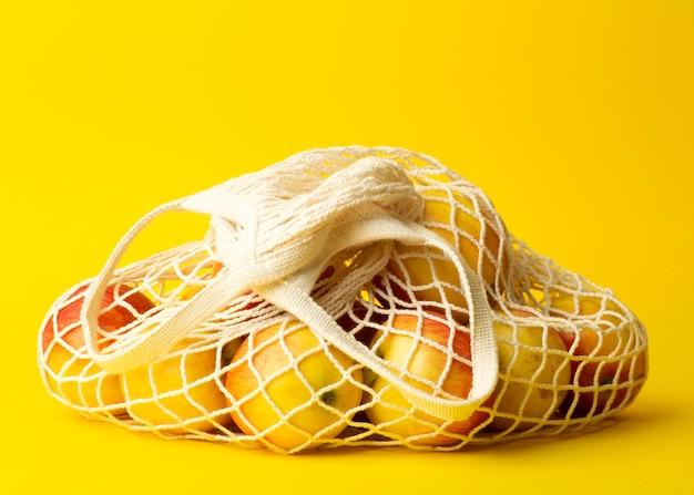 廃棄物ゼロのコンセプト。黄色の背景にひもの袋に入れたリンゴ。スーパーマーケットやショップのコンセプトにビニール袋はありません