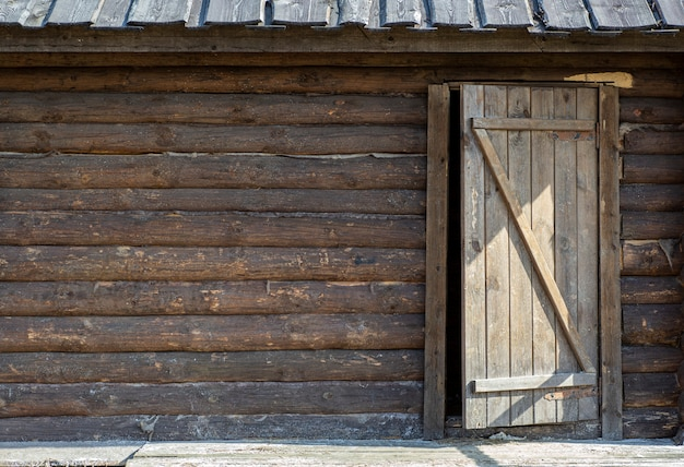 ドアと木製の背景。テクスチャとドアのある素朴な家の古い木製の壁