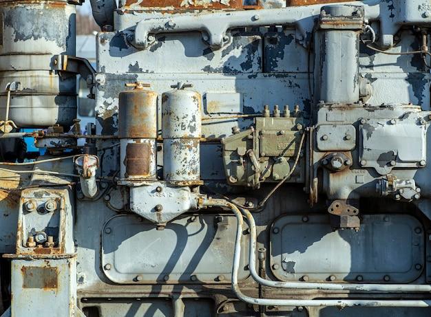 古いエンジンの背景。トラクターまたは列車の蒸気またはガスエンジンの古い金属片