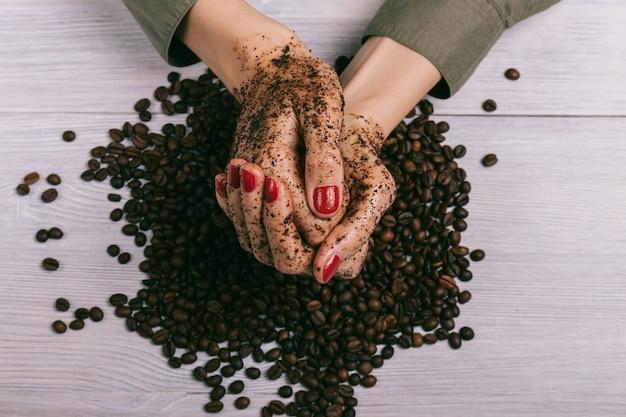 スクラブとコーヒー豆でコーティングされた女性の手のクローズアップ