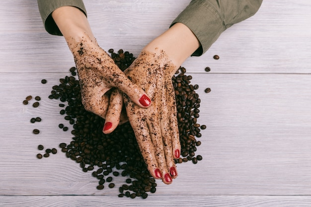 Молодая женщина, массируя руку с кофе скраб