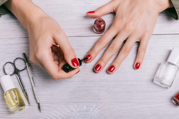 女性のクローズアップは赤いラッカーで彼女の爪を描きます