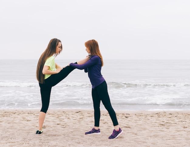 スポーツインストラクターは女の子がビーチでストレッチをするのを助けます