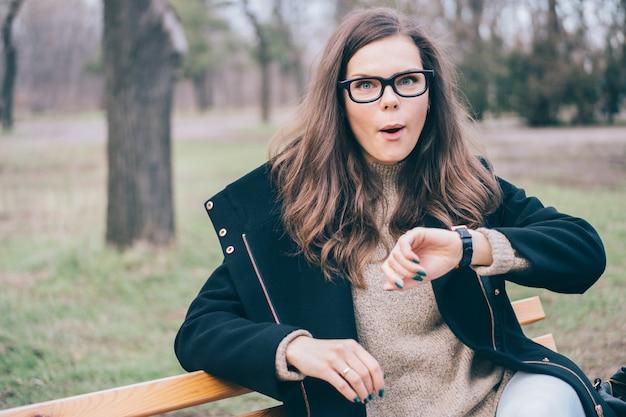Молодая привлекательная женщина проверяет время на наручных часах