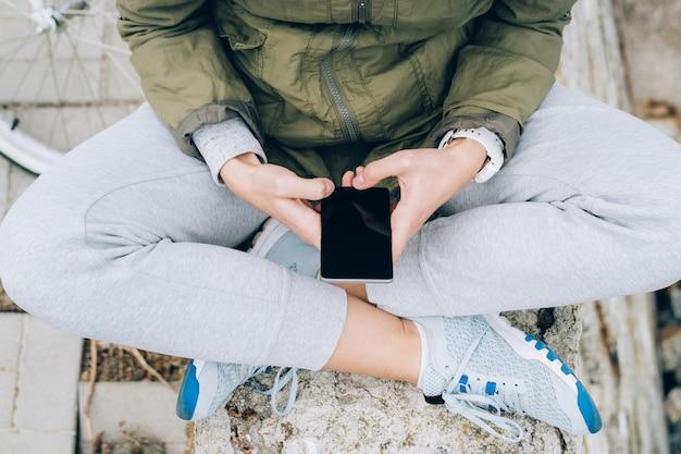 Мобильный телефон в женских руках на открытом воздухе