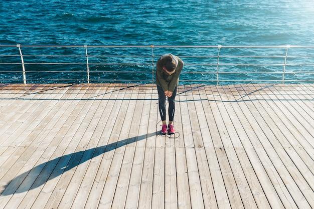 晴れた朝にウォーターフロントにロープをジャンプした後休んで若い運動女性