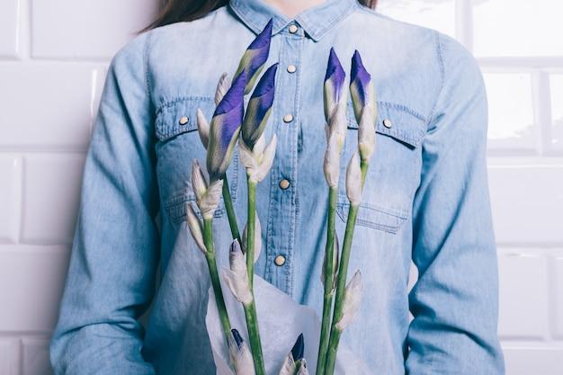 吹き飛ばされていない花アイリスの花束を保持しているデニムシャツの女性