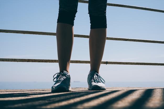 朝の太陽の下で青いスニーカーで細い女性の足