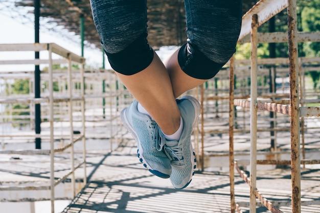 朝屋外でプルアップを行う運動の若い女性クローズアップ