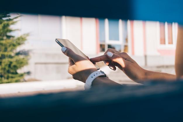 ベンチに座って携帯電話を楽しんでいる若い女性のクローズアップ