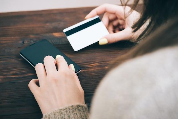 女性の画像をトリミングして、クレジットカードからスマートフォンに情報を入力します