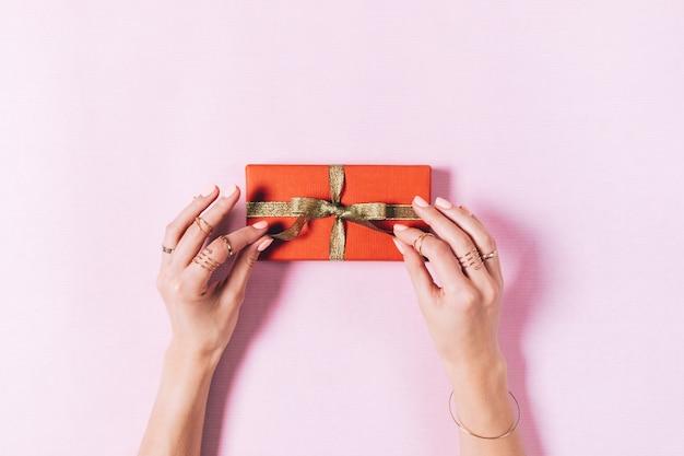 Вид сверху женских рук, связывающих бант на коробке с подарком