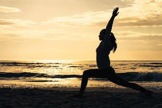 日の出の朝の体操中にビーチで女性のシルエット