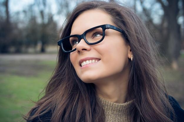 Портрет привлекательной молодой улыбающейся женщины с длинными каштановыми волосами в парке