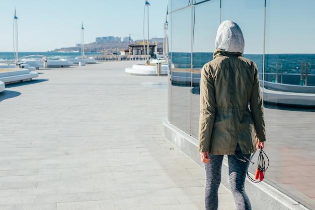 Спортивная девушка в капюшоне гуляет по побережью