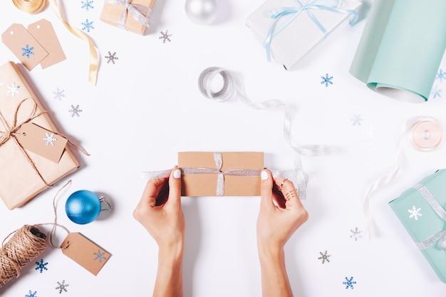 Женские руки, связывающие бантик на коробке с подарком