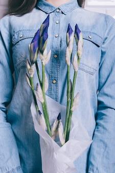 吹き飛ばされていない花アイリスの花束を保持しているデニムシャツの女の子のクローズアップ