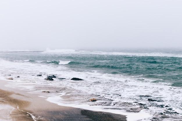 Вид на зимний пляж и море во время снегопада и ветра, пасмурный пейзаж