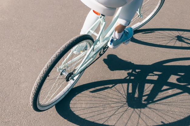 Вид со спины девушка едет на велосипеде по асфальту в солнечный день