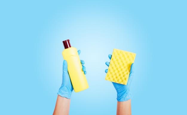 ゴム手袋の女性の手は、ボトルとスポンジに洗剤を保持します