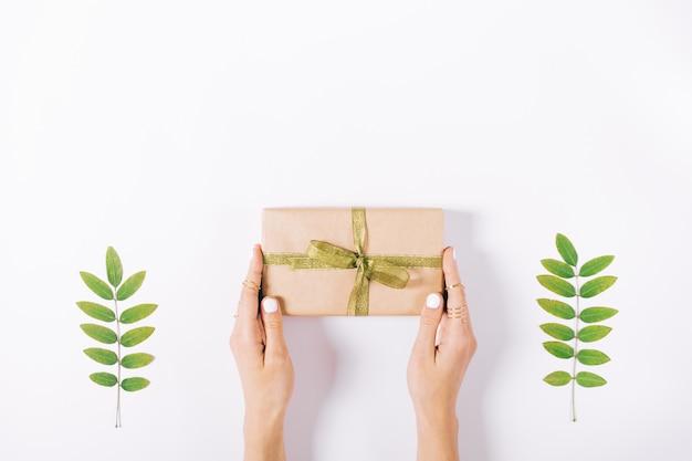 Женские руки держат коробку с подарком