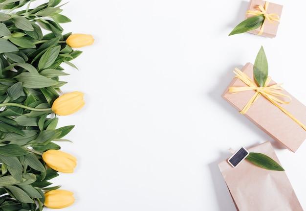 Желтые тюльпаны и коробка с подарками и лентами на белом