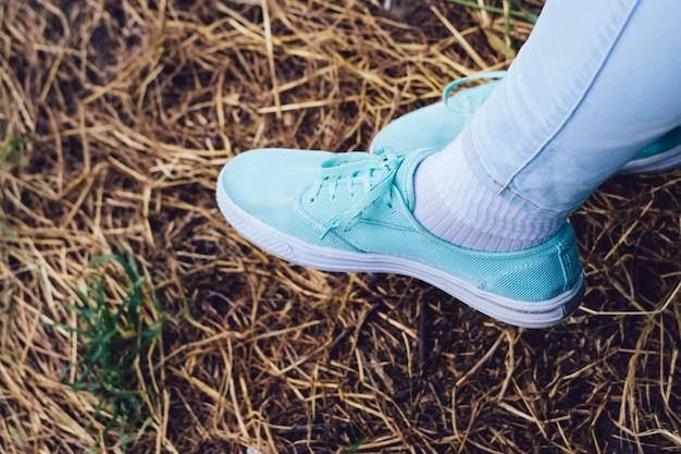 スニーカーと公園の乾いた草の背景にジーンズの女性の足