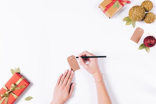 女性の手がクリスマスの飾りを準備しています