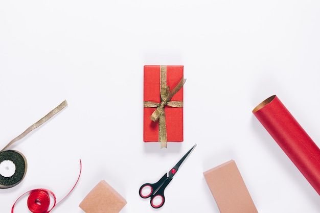 赤いギフトボックス、リボン、包装紙、はさみ