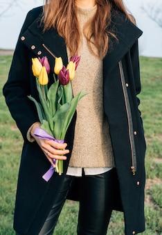 Молодая стройная женщина в пальто стоит на зеленом лугу и держит в руке букет тюльпанов