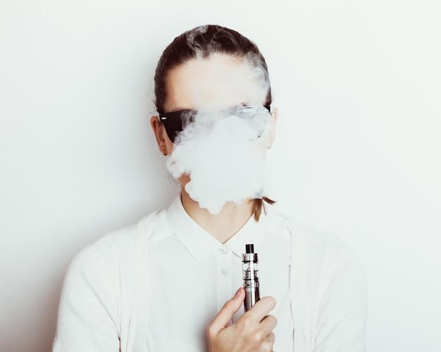 Женщина в очках курит электронную сигарету