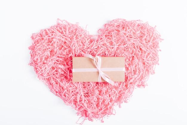 Розовое декоративное сердечко и коробка с подарком и лентой на белом фоне