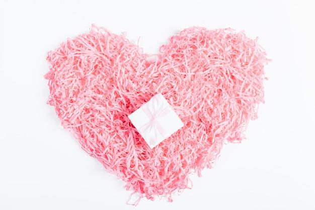 Вид сверху на розовое сердце и декоративную коробочку с подарком и лентой