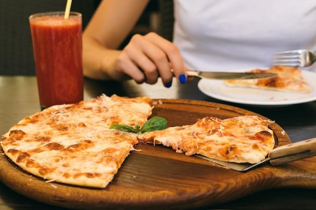 ピザとピザ屋のテーブルの上のトマトジュースのガラスを食べた