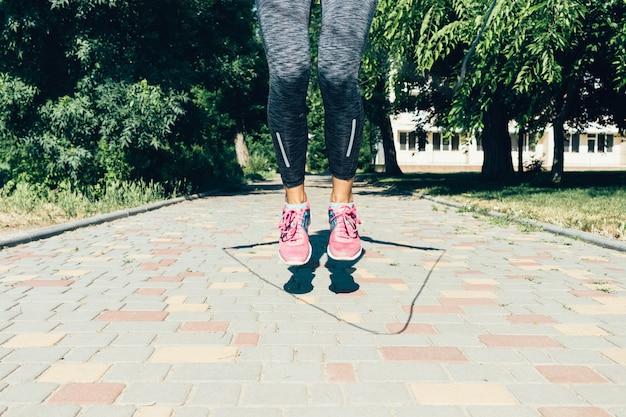Крупным планом женские ножки в кроссовках, прыжки через скакалку летом на открытом воздухе, низкий угол