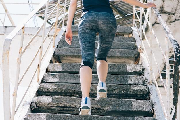 Стройная спортивная девушка поднимается по лестнице