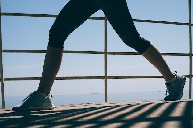Красивые стройные ноги молодой спортивной женщины в синих кроссовках на фоне моря в утреннем свете крупным планом
