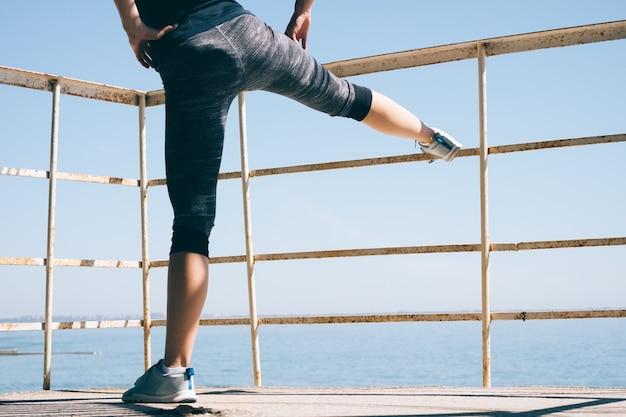 Молодая спортивная женщина, делающая ногу, растягивающуюся на пляже утром