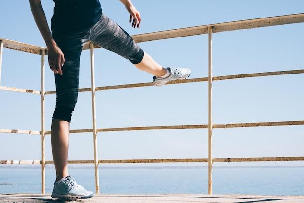 Молодая спортивная женщина делает растяжку на пляже по утрам