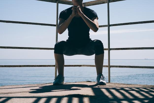 Спортивная (ый) молодая женщина, делая приседания утром на фоне моря, крупным планом
