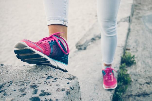 スニーカーとジーンズのコンクリート縁石の上に立っている女性の足