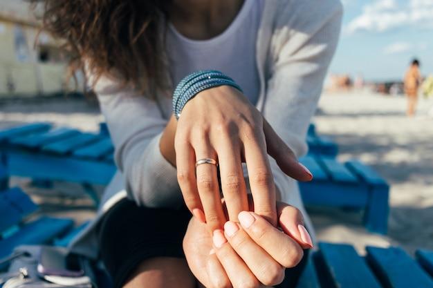ビーチのベンチに座っている彼女の指にリングを持つ女性