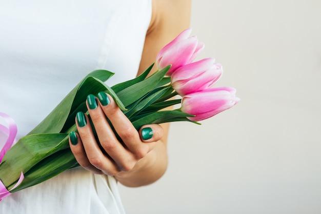 Девушка в белом платье держит тюльпаны на светлом фоне