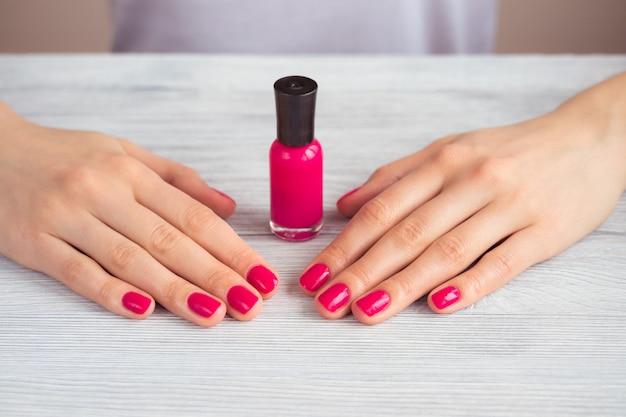 ピンクのマニキュアと木製のテーブルにラッカーの瓶を持つ女性の手