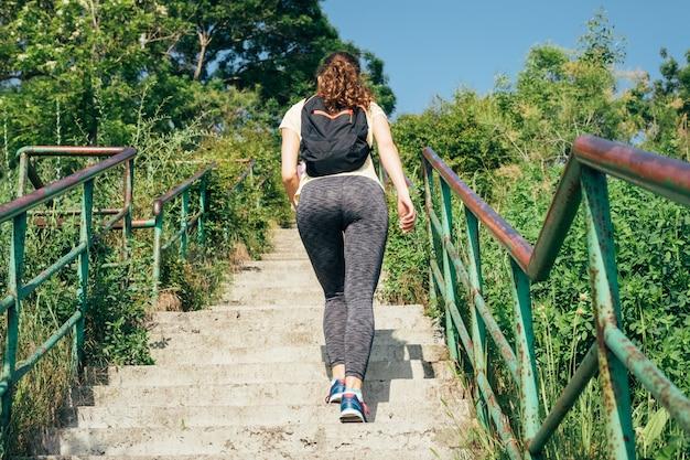 夏の屋外の階段を登るバックパックとスポーツウェアでスリムな女の子