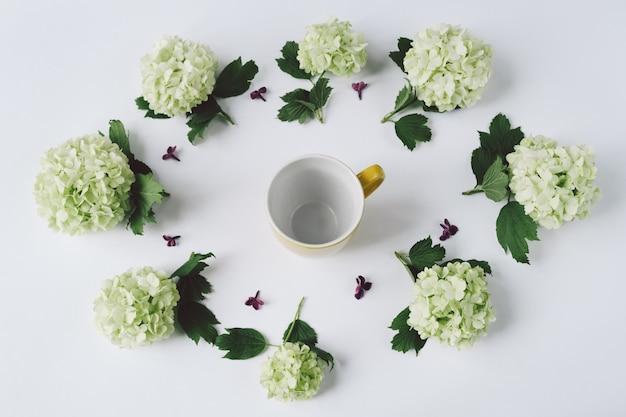 白い背景の上の黄色のカップの周りに横たわる円の形の緑の花
