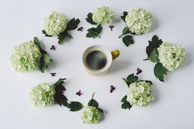 白い背景の上のコーヒーと黄色のカップの周りに横たわる円の形の緑の花