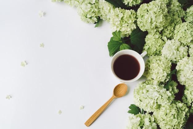 緑の花、紅茶と白い背景の上の木のスプーンで黄色のカップ