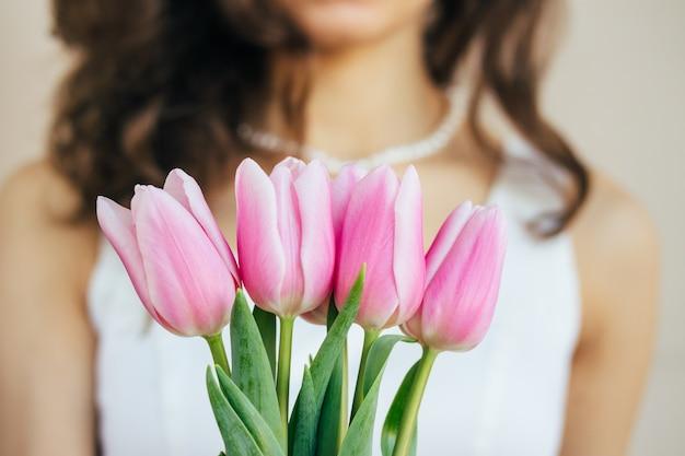 白いドレスの巻き毛を持つ美しい若い女の子の前にピンクのチューリップ