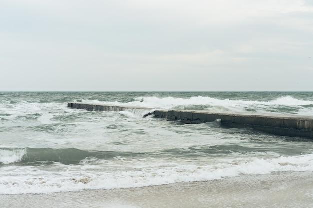 Морские волны разбиваются о бетонный волнорез в пасмурный день
